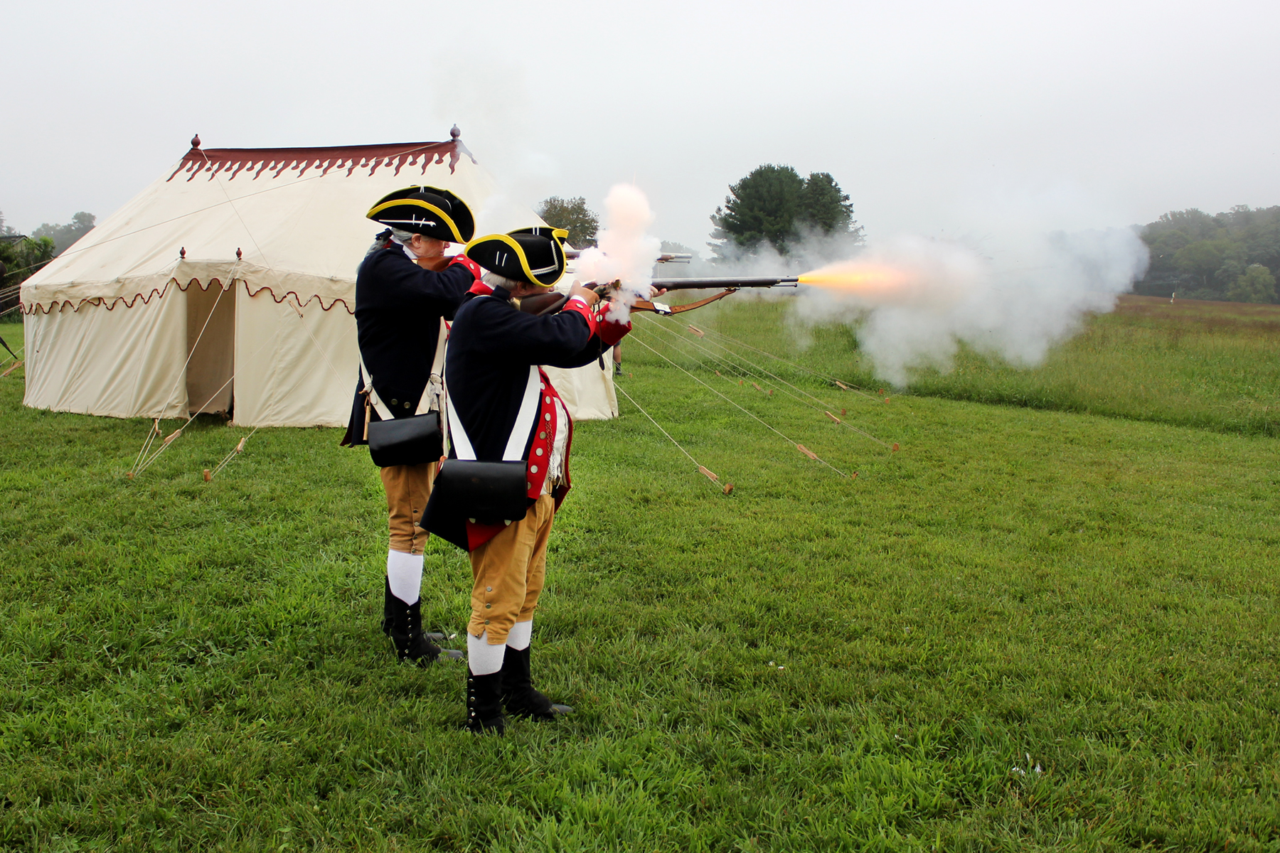 Reenactors from the 1st Delaware Regiment firing off a few rounds from their muskets, with a replica of George Washington's tent in the background, courtesy of the Museum of the American Revolution.