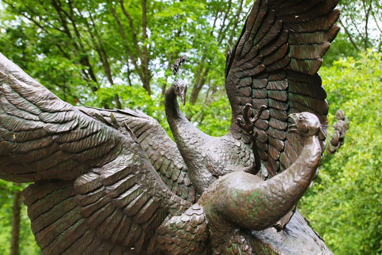 Close up shot of a bronze sculpture of two life-size fighting peacocks in front of the Brandywine's main entrance