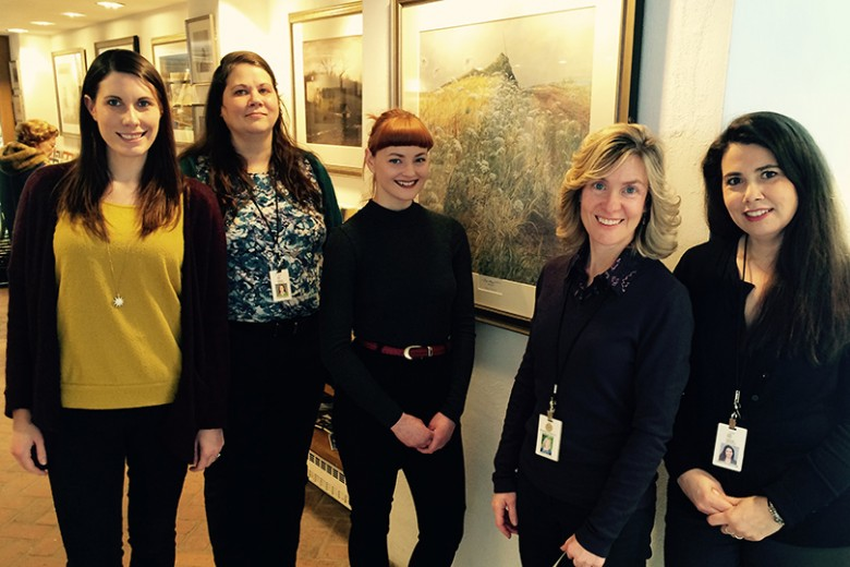 shop staff in front of August print