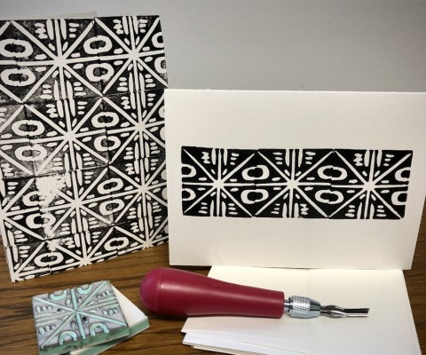 Black and white printed design on a white notecard, featured alongside printmaking tools and supplies