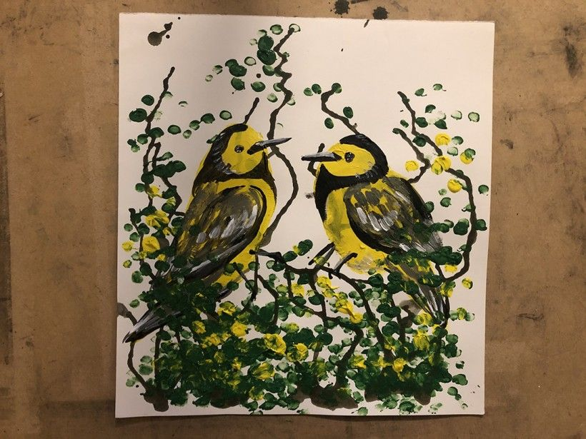 Two yellow painted birds made using a potato-printing technique