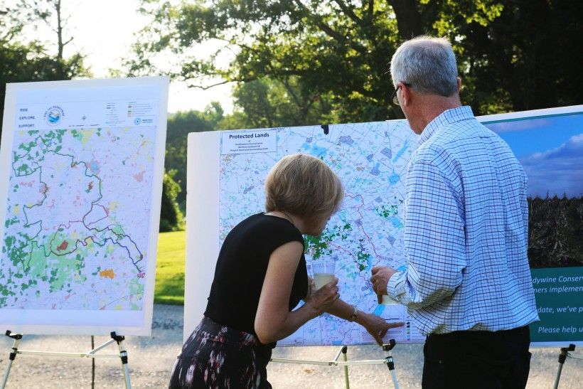Two people viewing a map of protected lands Farm to Table dinner to celebrate the 50th anniversary of the Brandywine Conservancy