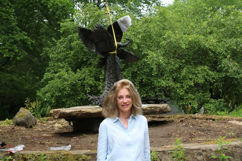 """Rikki Morley Saunders standing in front of """"Tipping Point"""" sculpture during its installation at the Brandywine"""