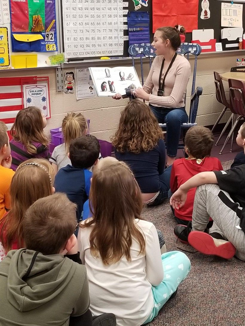 "A middle school student reads ""Little Penguin Gets the Hiccups"" to first graders at Laurel Valley Elementary School."