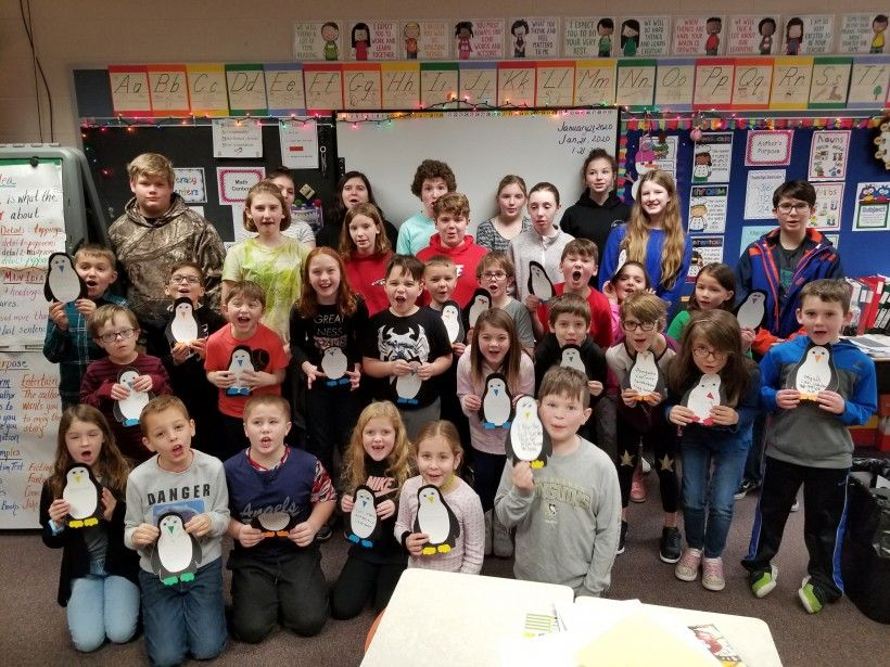 Laurel Valley Middle School students line up behind a class of second graders, who are displaying the penguins they made, at R.K. Mellon Elementary School.