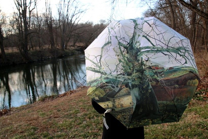 Woman modeling an umbrella featuring artist Andrew Wyeth's painting entitled Pennsylvania Landscape next to the Brandywine River