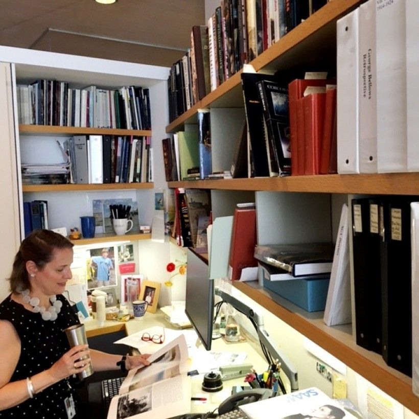 Curator Sarah Cash drinking coffee in her office