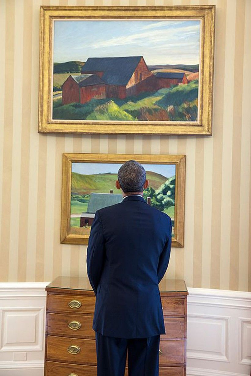 President Barack Obama looks at the Edward Hopper paintings now displayed in the Oval Office, Feb. 7, 2014. The paints are Cobb's Barns, South Truro, top, and Burly Cobb's House, South Truro. (Official White House Photo by Chuck Kennedy)