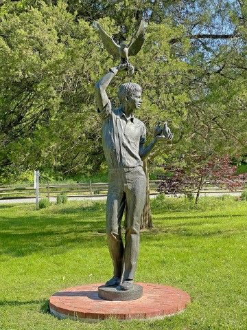 Outdoor bronze sculpture of a larger-than-life young man holding two doves in one hand and a hawk in the other.