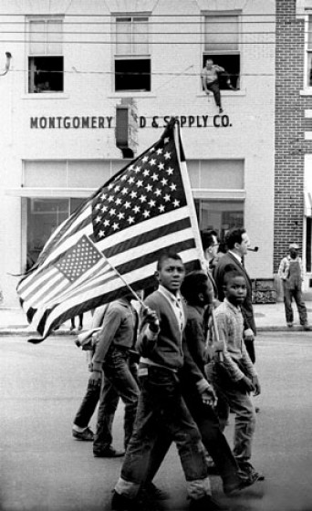 Young civil rights activists with American flags march towards the State Capital Building.